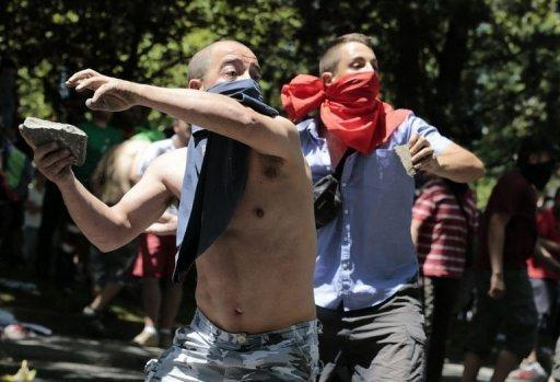Demonstrators throw rocks at riot policemen during a miners' demonstration in Madrid