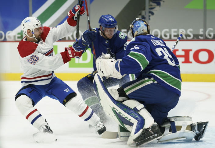 Vancouver Canucks defenseman Tyler Myers (57) stops Montreal Canadiens left wing Tomas Tatar (90) from getting a shot on Canucks goaltender Thatcher Demko (35) during the first period of an NHL hockey game Thursday, Jan. 21, 2021, in Vancouver, British Columbia. (Jonathan Hayward/The Canadian Press via AP)