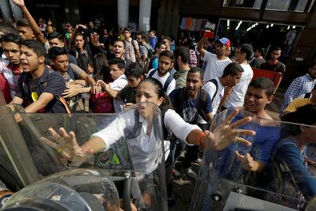 Opposition supporters clash with riot police in front of a courthouse in Caracas