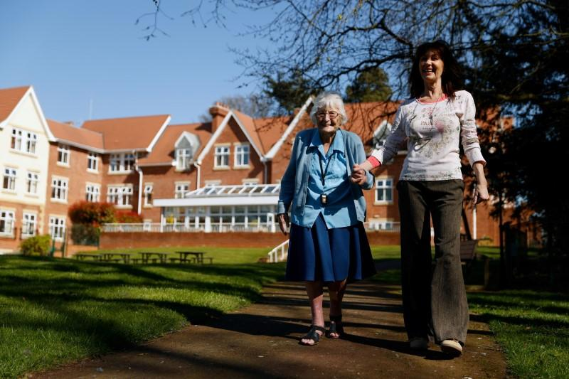 Resident Roche takes a walk in the grounds of Foxholes Care Home, assisted by activities director Davies