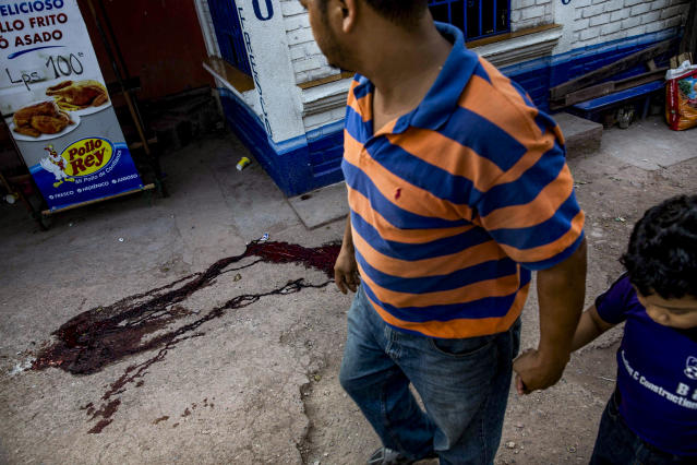 <p>Father and son pass by a pool of blood left by the body of a 20 year<br>old boy killed few hours before in Tegucigalpa, Honduras. (Photo: Francesca Volpi) </p>