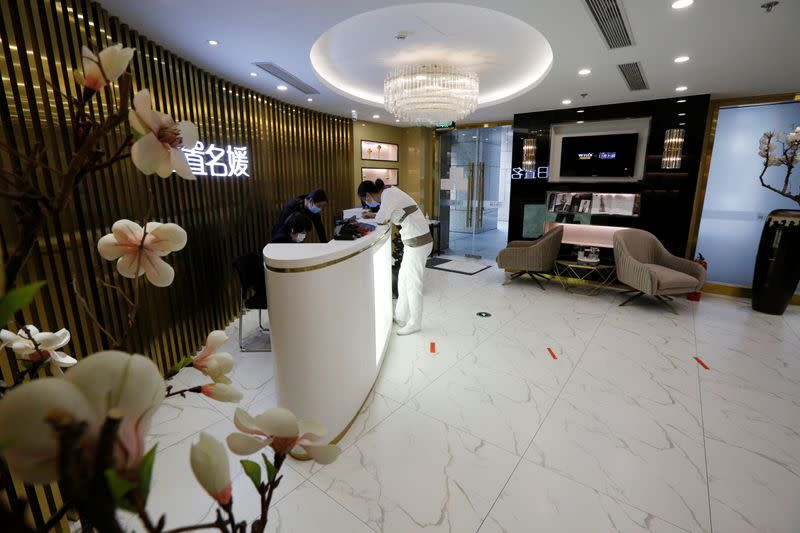 Staff members wearing face masks are seen at the reception area of the Pearl Deluxe beauty spa as the country is hit by an outbreak of the novel coronavirus, in Beijing