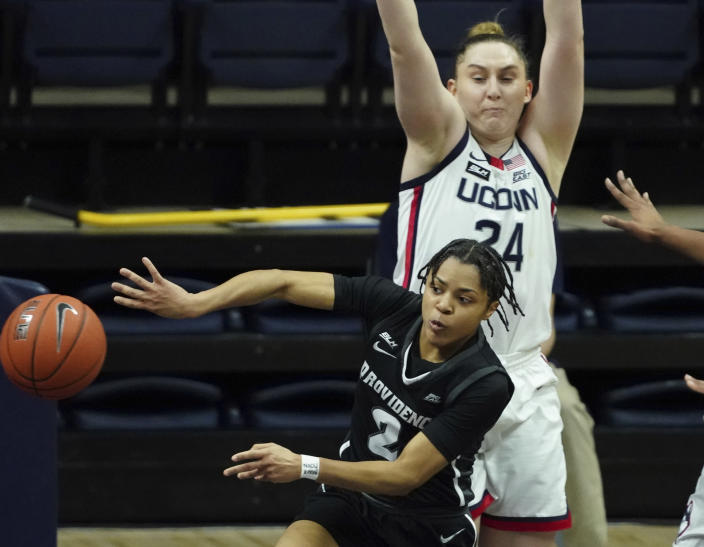 Providence guard Chanell Williams (2) passes the ball as Connecticut guard Anna Makurat (24) defends in the first half of an NCAA college basketball game at Harry A. Gampel Pavilion, Saturday, Jan. 9, 2021, in Storrs, Conn. (David Butler II/Pool Photo via AP)