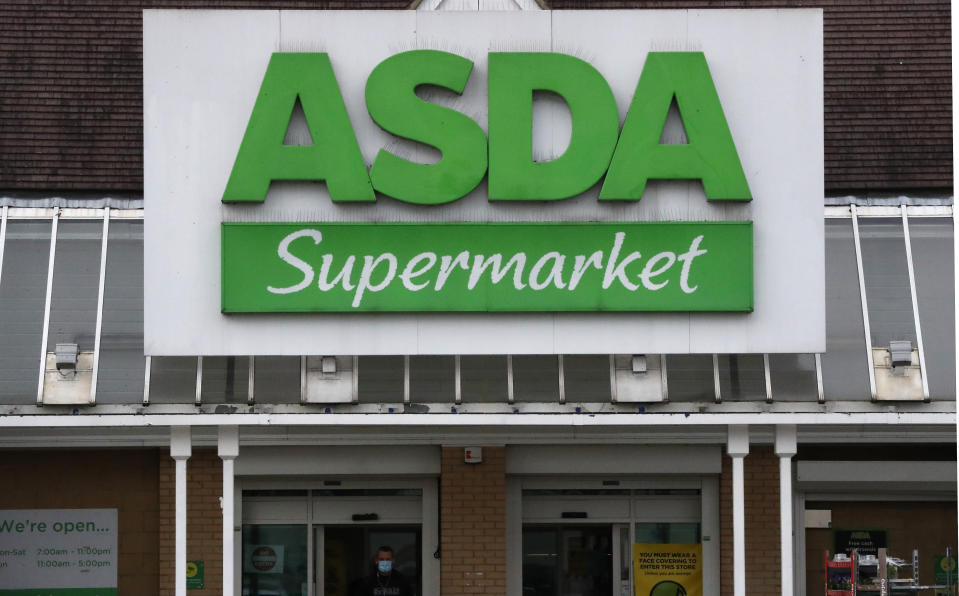 The entrance of an ASDA supermarket in London, Friday, March 26, 2021. More than 40,000 store workers at Asda, Britain's third-largest supermarket chain, can proceed with their longstanding claim for equal pay following a ruling from the country's Supreme Court. The workers, around two-thirds of whom are women, first brought their sex discrimination claim in 2014. (AP Photo/Frank Augstein)