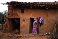 A woman watches health workers leaving, standing in front of her house at Jamsoti village, Uttar Pradesh state, India, on June 8, 2021. India's vaccination efforts are being undermined by widespread hesitancy and fear of the jabs, fueled by misinformation and mistrust. That's especially true in rural India, where two-thirds of the country's nearly 1.4 billion people live. (AP Photo/Rajesh Kumar Singh)