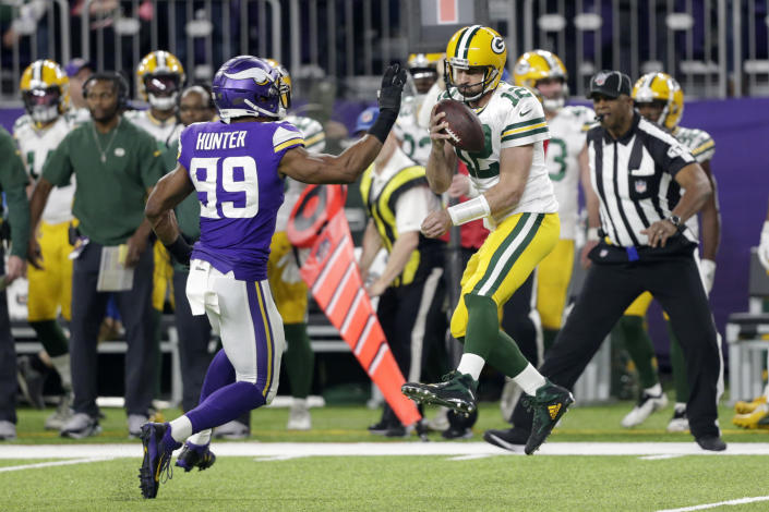Green Bay Packers quarterback Aaron Rodgers (12) is about to be sacked by Minnesota Vikings defensive end Danielle Hunter (99) during the first half of an NFL football game Monday, Dec. 23, 2019, in Minneapolis. (AP Photo/Andy Clayton-King)