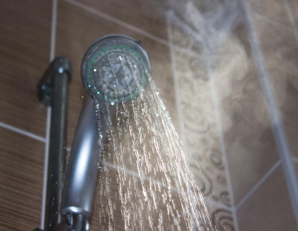 Low angle view of flowing shower head in the bathroom. Horizontal composition. Image taken indoors and developed from Raw format. Focus on water. Shower head and other background are blurred.
