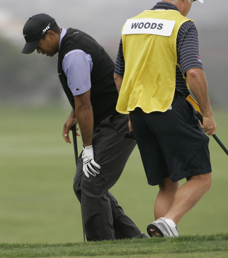 FILE - In this June 14, 2008 file photo, Tiger Woods holds onto his knee as he comes out of a bunker on the fourth hole during the third round of the US Open championship at Torrey Pines Golf Course in San Diego. Only after Tiger Woods captured the 2008 U.S. Open at Torrey Pines did anyone realized how unlikely it was that he even played.   (AP Photo/Charlie Riedel, File)