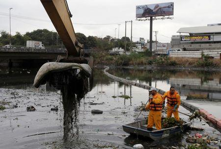 Men work cleaning up the garbage next to an ecobarrier at Meriti River which flows into Guanabara Bay, in Duque de Caxias, near Rio de Janeiro
