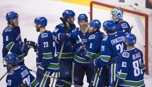 The Vancouver Canucks celebrate a win over the Buffalo Sabres in an NHL hockey game Friday, Jan. 18, 2019, in Vancouver, British Columbia. (Jonathan Hayward/The Canadian Press via AP)