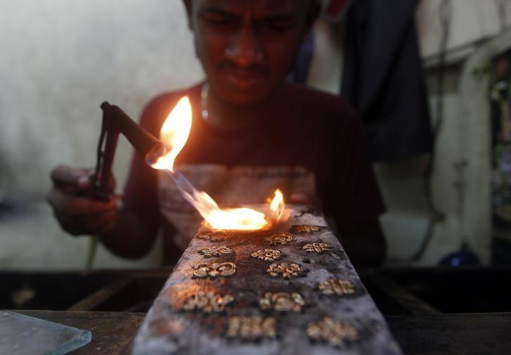 An employee makes gold studs at a jewellery workshop in Colombo