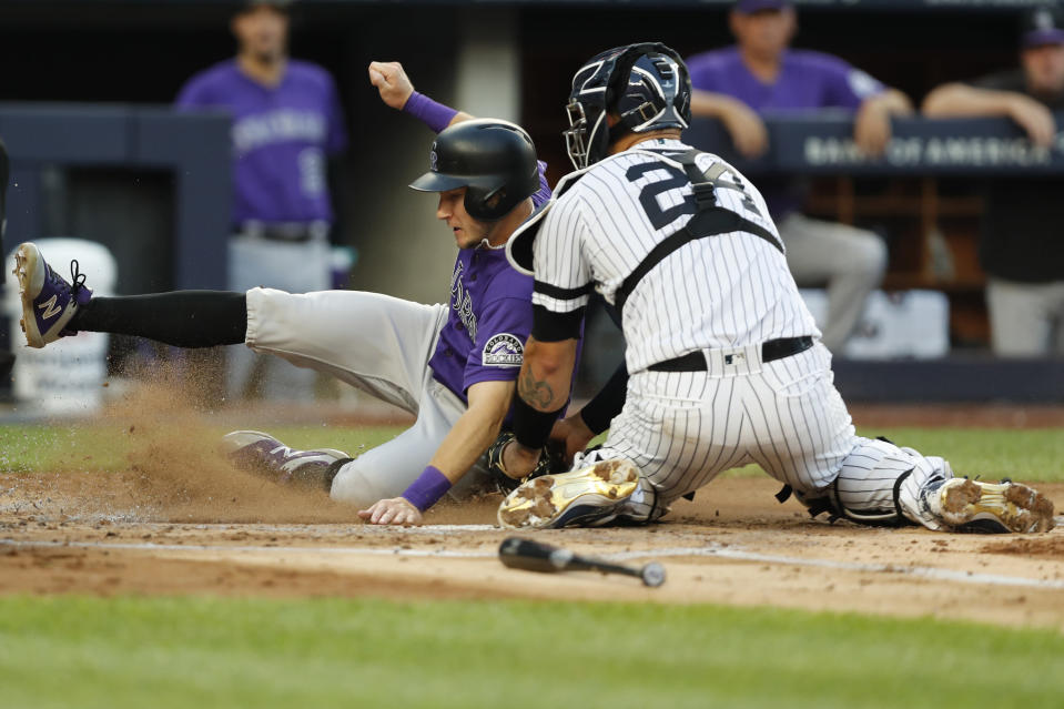 New York Yankees catcher Gary Sanchez (24) tags out Colorado Rockies' Garrett Hampson, who tried to score on a fly out by Charlie Blackmon during the second inning of a baseball game Friday, July 19, 2019, in New York. (AP Photo/Kathy Willens)
