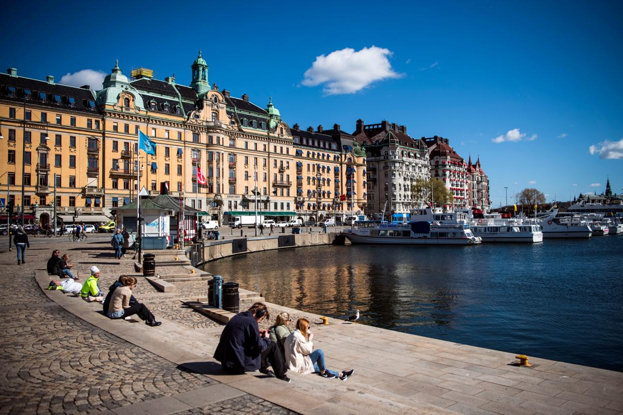 People enjoy the spring weather as they sit at Nybroplan in Stockholm on April 15, 2020, during the coronavirus COVID-19 pandemic. (Photo by Jonathan NACKSTRAND / AFP) (Photo by JONATHAN NACKSTRAND/AFP via Getty Images)
