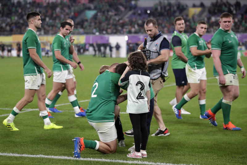 Ireland's Rory Best comforts his children after the Rugby World Cup quarterfinal match at Tokyo Stadium between New Zealand and Ireland in Tokyo, Japan, Saturday, Oct. 19, 2019. New Zealand won 46-14. (AP Photo/Jae C. Hong)