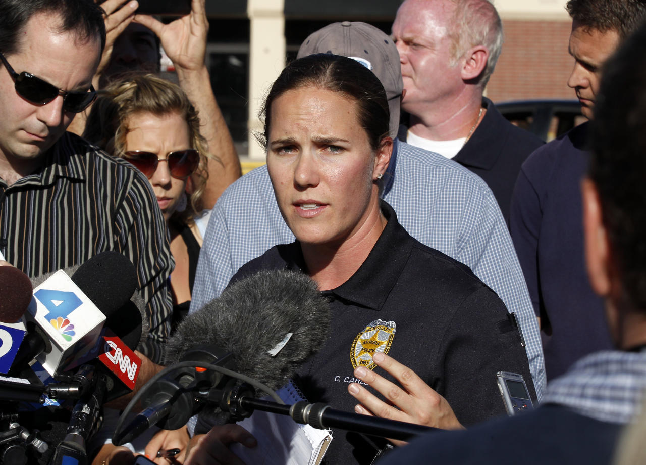 "Sgt. Cassidy Carlson, center, spokesperson for the Aurora Police Department, speaks during a media availability near the apartment of alleged gunman James Holmes, Saturday, July 21, 2012, in Aurora, Colo. Authorities reported that 12 people died and dozens more were shot during an assault at a movie theater midnight premiere of ""The Dark Knight Rises."" (AP Photo/Alex Brandon)"