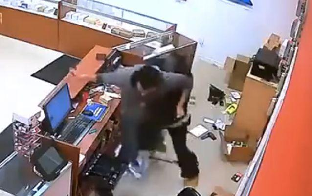 The robber wrestles to get his gun back off the shop assistant. Source: LiveLeak.