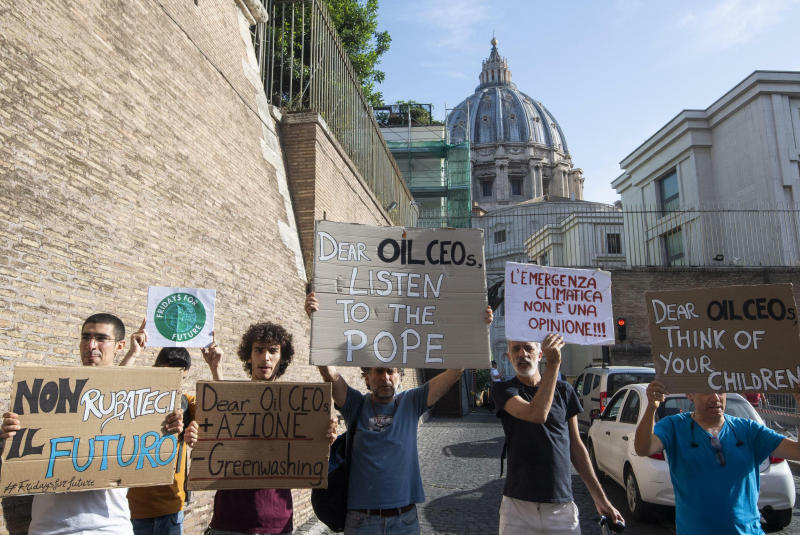 """Activists hold up signs outside the Vatican as Pope Francis meets with oil executives, Friday, June 14, 2019. The meeting marked the second year that Francis has invited oil and financial sector executives to the Vatican to impress upon them his concern that preserving God's creation is one of the fundamental challenges facing humankind today. Signs in Italian read """"Don't steal our future"""", left, and """"Climate emergency is not an opinion!"""", second from right.  (Claudio Peri/ANSA via AP)"""