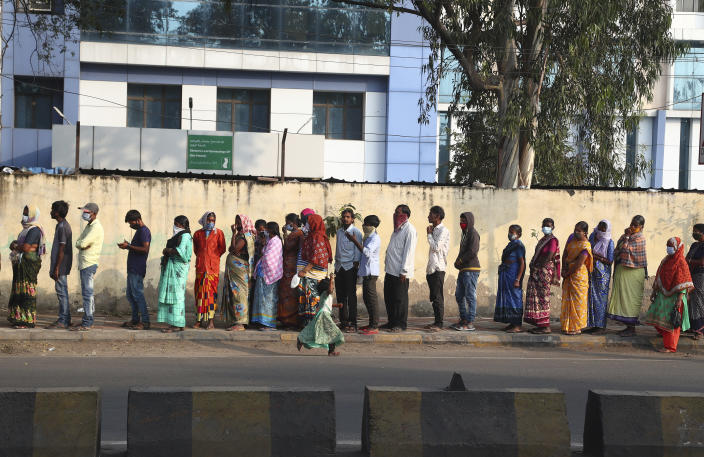 Indians wearing face masks as a precaution against coronavirus stand in a queue to receive free food outside a maternity hospital in Hyderabad, India, Monday, Jan. 18, 2021. India started inoculating health workers Saturday in what is likely the world's largest COVID-19 vaccination campaign, joining the ranks of wealthier nations where the effort is already well underway. (AP Photo/Mahesh Kumar A.)