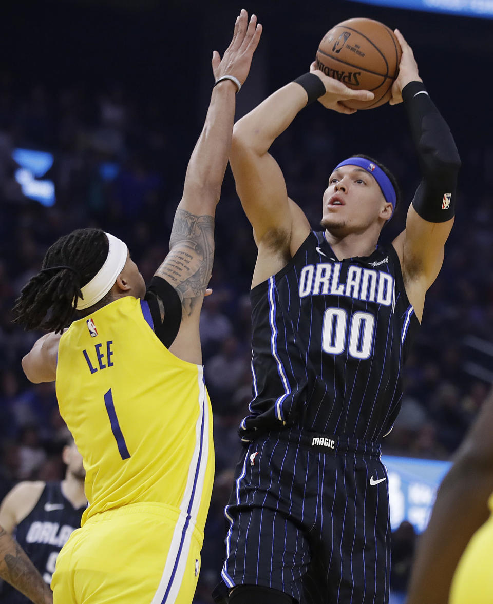 Orlando Magic's Aaron Gordon, right, shoots against Golden State Warriors' Damion Lee, left, bin the first half of an NBA basketball game Saturday, Jan. 18, 2020, in San Francisco. (AP Photo/Ben Margot)