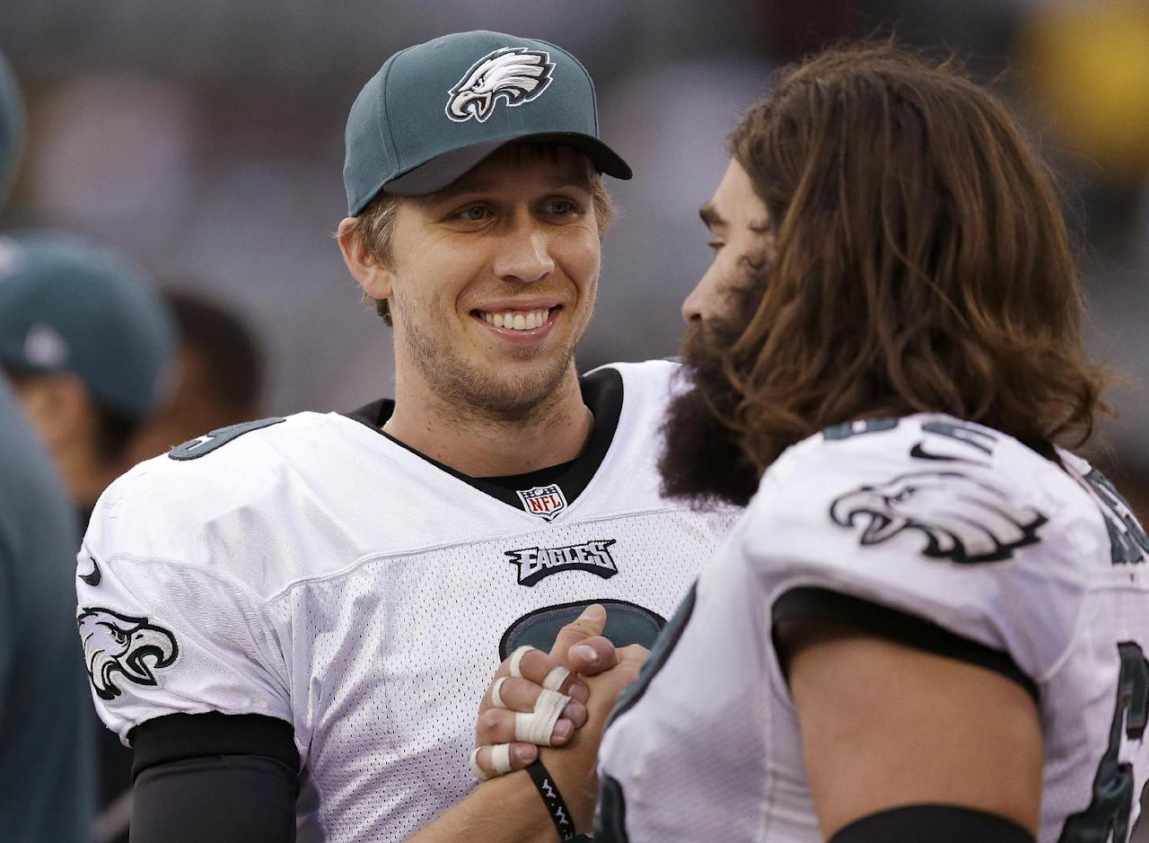 Philadelphia Eagles quarterback Nick Foles, left, smiles as he celebrates with center Jason Kelce during the fourth quarter of an NFL football game against the Oakland Raiders in Oakland, Calif., Sunday, Nov. 3, 2013. The Eagles won 49-20. (AP Photo/Ben Margot)