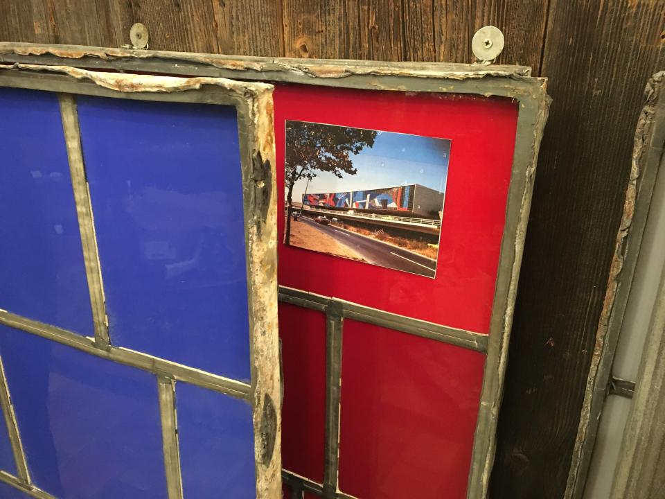 This Oct. 15, 2019 photo shows stained glass windows, salvaged from the old American Airlines terminal (Terminal 8) at John F. Kennedy International Airport in New York, along with an image of the terminal when the windows were still in place. They are available for sale at Olde Good Things salvage store in New York. (Katherine Roth via AP)