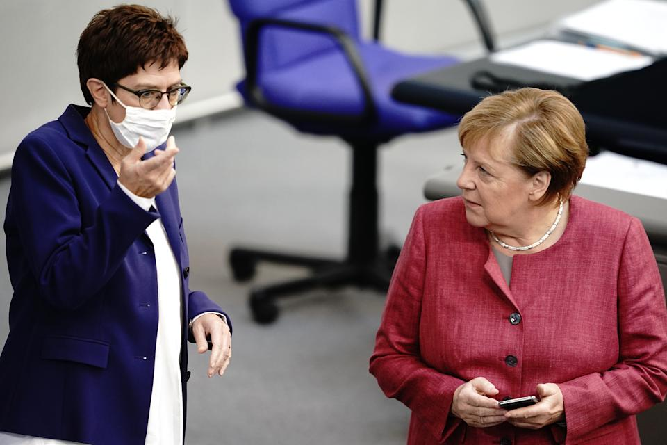 30 September 2020, Berlin: Chancellor Angela Merkel (CDU) talks to CDU Chairwoman and Federal Minister of Defence Annegret Kramp-Karrenbauer (l) during the general debate on the federal budget in the Bundestag. Photo: Kay Nietfeld/dpa (Photo by Kay Nietfeld/picture alliance via Getty Images)