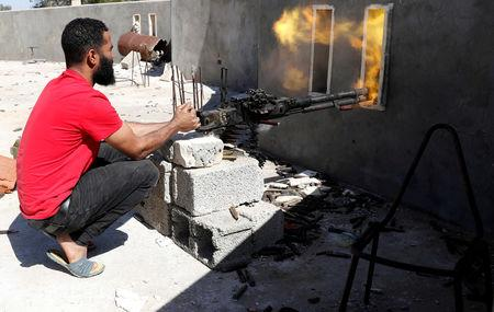 FILE PHOTO: A fighter loyal to Libyan internationally recognised government fires a heavy machine gun during clashes with forces loyal to Khalifa Haftar at outskirts of Tripoli, Libya May 16, 2019. REUTERS/Goran Tomasevic/File Photo