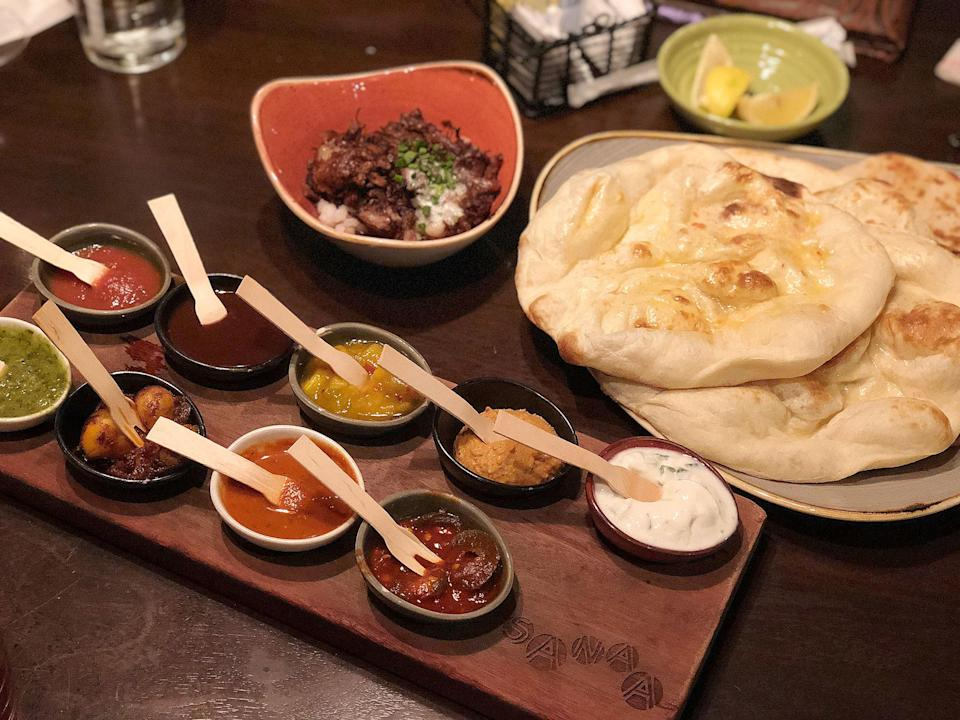 """<p><strong>Where to Get It: </strong>Sanaa Lounge at Animal Kingdom Lodge ($13-$15) <strong>Lou's Review: </strong>""""For me, nothing complements a day in the parks better than a late-night trip to this spot for some carbs. For me, the bread service alone is worth the trip. The art of African cooking with Indian flavors is embodied in this grand display of a variety of breads (traditional naan, garlic-ginger naan, spiced naan, onion kucha, and paneer paratha) and accompaniments (roasted red pepper hummus, mango chutney, tomato-date jam, tamarind chutney, coriander chuntey, garlic pickle, red chile sambal, and spicy jalapeño-lime pickle.) You can order your choice of 3 accompaniments for $13, but I highly recommend spending an additional $2 to get all 9 accompaniments. The flavors range in degrees of space and heat, but there is something about the shared experience of literally breaking bread and sampling the flavors that makes this a can't-miss item. (Note: This is also a wonderful vegetarian option.)<i>""""</i></p>"""