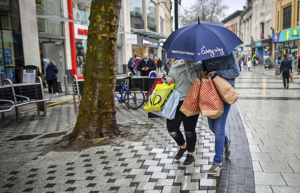 "Shoppers loaded with bags and an umbrella to protect against the falling rain, in the centre of Cardiff, Wales, Friday Nov. 20, 2020, where shops are open and people are out in numbers taking advantage of buying nonessential items in the run-up to Christmas. Restrictions across Wales have been relaxed following a two-week ""firebreak"" lockdown to stem spread of the coronavirus. (Ben Birchall/PA via AP)"