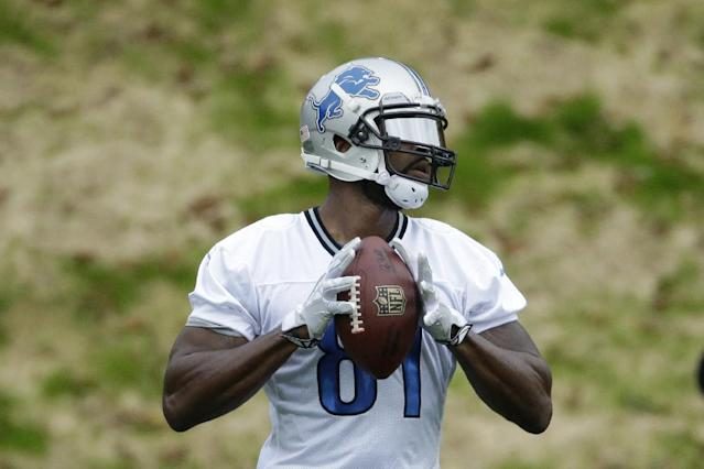 Detroit Lions wide receiver Calvin Johnson, who is recovering from an injury, prepares to throw a ball during a training session at Pennyhill Park Hotel in Bagshot, England, Thursday, Oct. 23, 2014. The Atlanta Falcons will play the Detroit Lions in an NFL football game at London's Wembley Stadium on Sunday. (AP Photo/Matt Dunham)