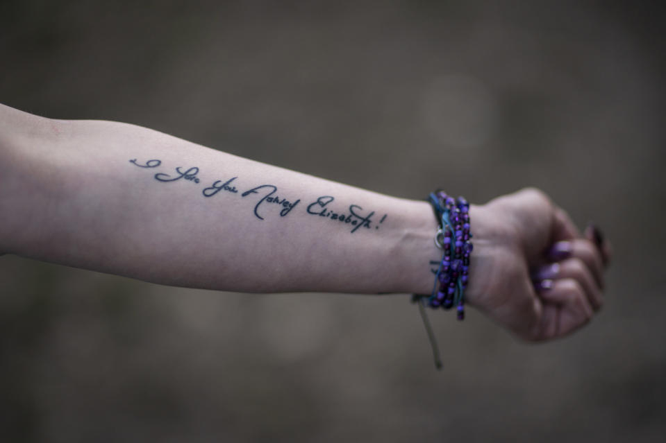 """Ashley Ellis, 34, shows a tattoo of a handwritten note from her fiancé, Brandon Williams, on her arm, Tuesday, March 16, 2021, in Huntington, W.Va. Ellis started using drugs in college and has tried many times to stop using. She met the love of her life, Williams, when they were both in recovery. """"He had the most beautiful soul of anyone I've ever known,"""" she said. But shortly after their child was born, they both relapsed. Williams died of an overdose. Now she's determined to remain in recovery. """"I think losing Brandon has been, quite possibly, what's going to save my life."""" (AP Photo/David Goldman)"""