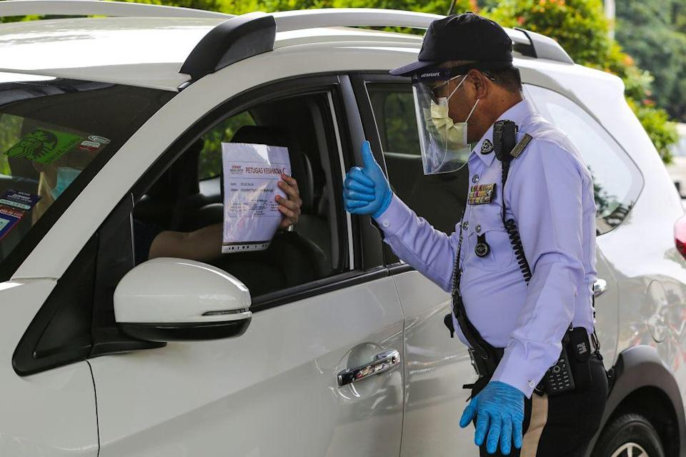 A traffic policeman conducts checks on vehicles during a roadblock on Jalan Sultan Ismail in Kuala Lumpur October 14, 2020. Datuk Seri Ismail Sabri Yaakob said letters from employers were only for work purposes. — Picture by Yusof Mat Isa