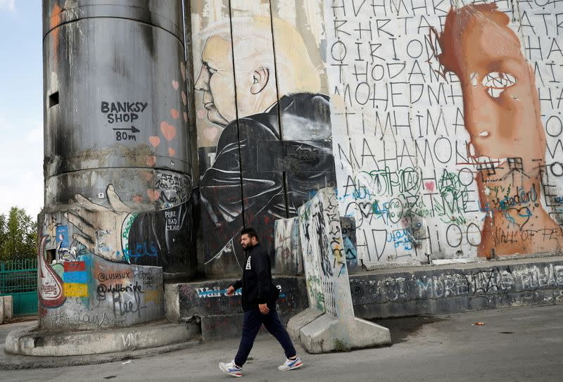 A Palestinian man walks past an anti-U.S. President Donald Trump mural which was painted on a section of the Israeli barrier, in Bethlehem in the Israeli-occupied West Bank