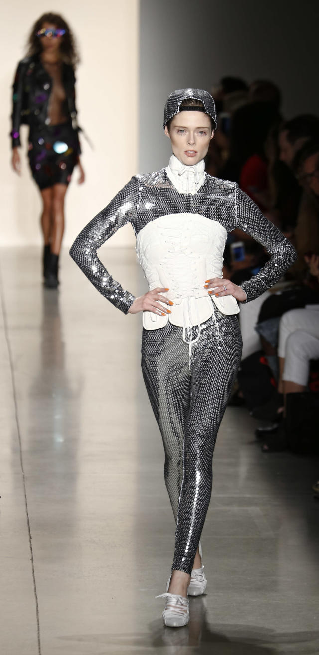 Coco Rocha wears a full sequin bodysuit, hat, and white corset at the Jeremy Scott show. (Photo: Getty)