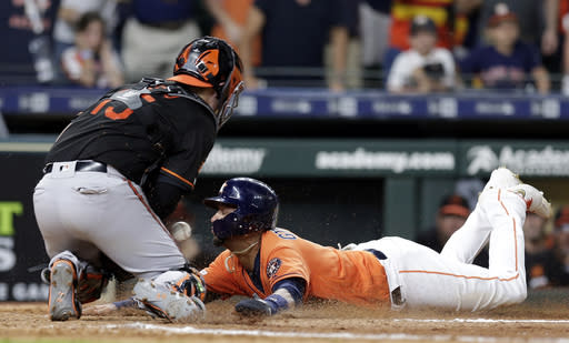 Houston Astros Yuli Gurriel slides into home plate as Baltimore Orioles catcher Chance Sisco, left, bobbles the ball allowing Gurriel to score the winning run during the 11th inning of a baseball game Friday, June 7, 2019, in Houston. (AP Photo/Michael Wyke)