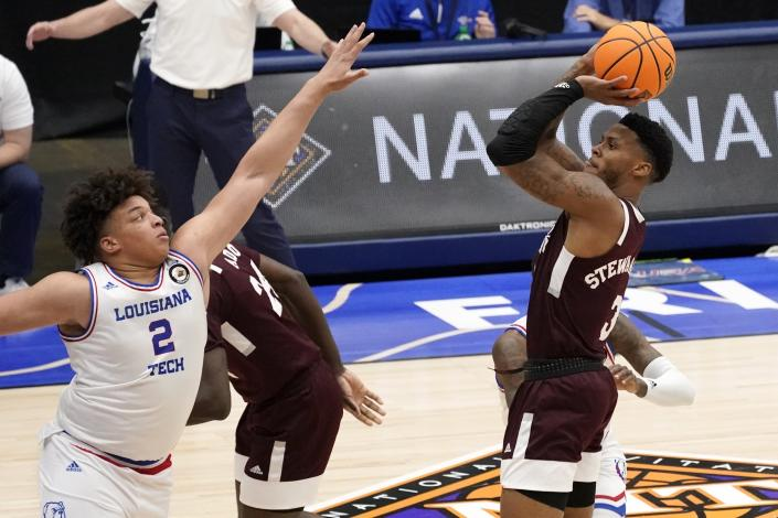 Louisiana Tech forward Kenneth Lofton Jr., left, defends as Mississippi State guard D.J. Stewart Jr., right, shoots and sinks a 3-point basket in the first half of an NCAA college basketball game in the semifinals of the NIT, Saturday, March 27, 2021, in Frisco, Texas. (AP Photo/Tony Gutierrez)