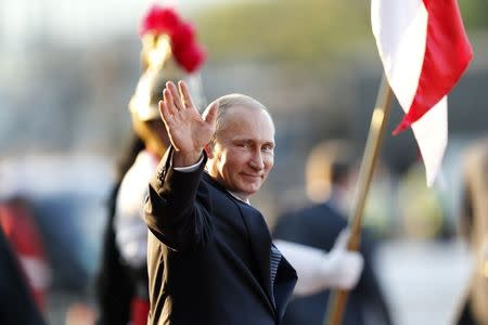 Russia's President Vladimir Putin waves as he leaves the Itamaraty Palce after the 6th BRICS summit and the Union of South American Nations (UNASUR), in Brasilia