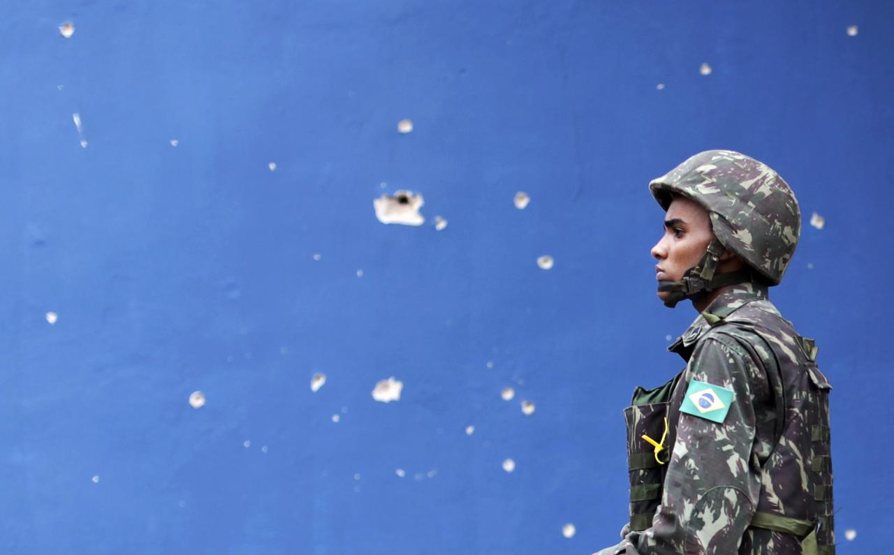 A Brazilian Army soldier walks past bullet holes in a wall during an operation in the Mare slums complex in Rio de Janeiro March 26, 2014. Brazil will deploy federal troops to Rio de Janeiro to help quell a surge in violent crime following attacks by drug traffickers on police posts in three slums on the north side of the city, government officials said on Friday.