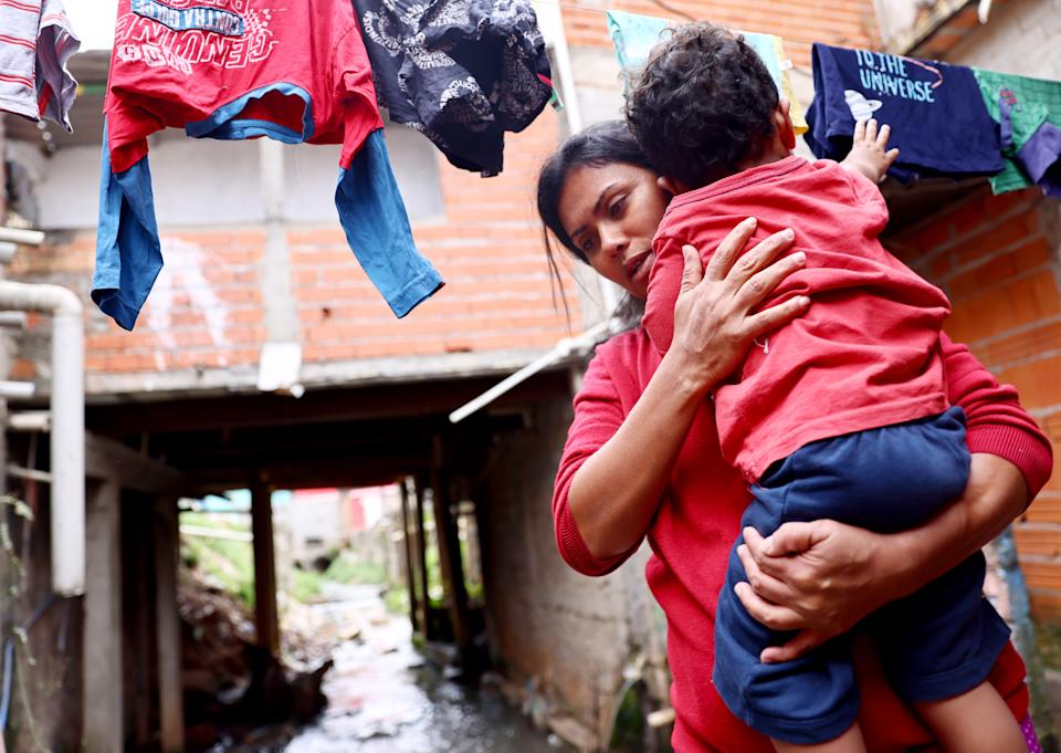 SAO PAULO, BRAZIL - MAY 15: Francisca Cristiane carries her son  Artur outside her home in the Brasilandia neighborhood amid the COVID-19 pandemic on May 15, 2021 in Sao Paulo, Brazil. She said she won't send her children to school because of COVID-19 fears. Health experts are warning that Brazil should brace for a new surge of COVID-19 amid a slow vaccine rollout and relaxed restrictions. The state of Sao Paulo has registered over 3 million cases of COVID-19 and more than 100,000 deaths. Residents of Brasilandia suffered some of the highest death rates in Sao Paulo due to COVID-19 last year. Over 430,000 people have been killed in Brazil by COVID-19, second only to the U.S. (Photo by Mario Tama/Getty Images)