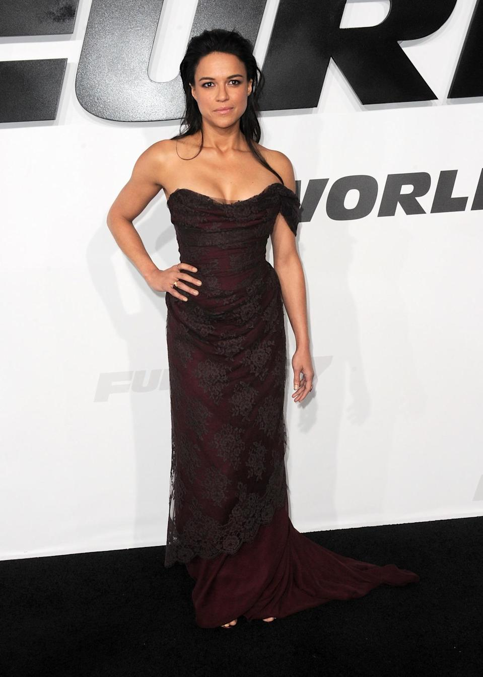 """Michelle Rodriguez in this wine colored gown is definitely a style departure for the actress — but one that should be repeated regularly. The strapless Vivenne Westwood dress is fitted, featuring the designer's signature corseted top, and the lace overlay adds some """"Downton Abbey""""-inspired elegance."""
