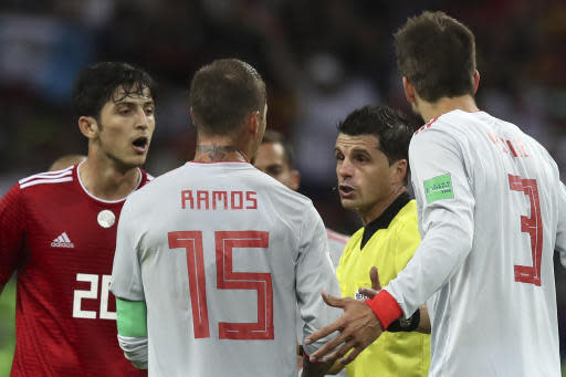Referee Andres Cunha from Uruguay, second right, talks to Spain's Sergio Ramos, center, Spain's Gerard Pique, right, and Iran's Sardar Azmoun during the group B match between Iran and Spain at the 2018 soccer World Cup in the Kazan Arena in Kazan, Russia, Wednesday, June 20, 2018. (AP Photo/Thanassis Stavrakis)