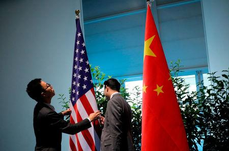 FILE PHOTO: Chinese officials prepare the flags for the China-U.S. bilateral meeting at the G20 leaders summit in Hamburg