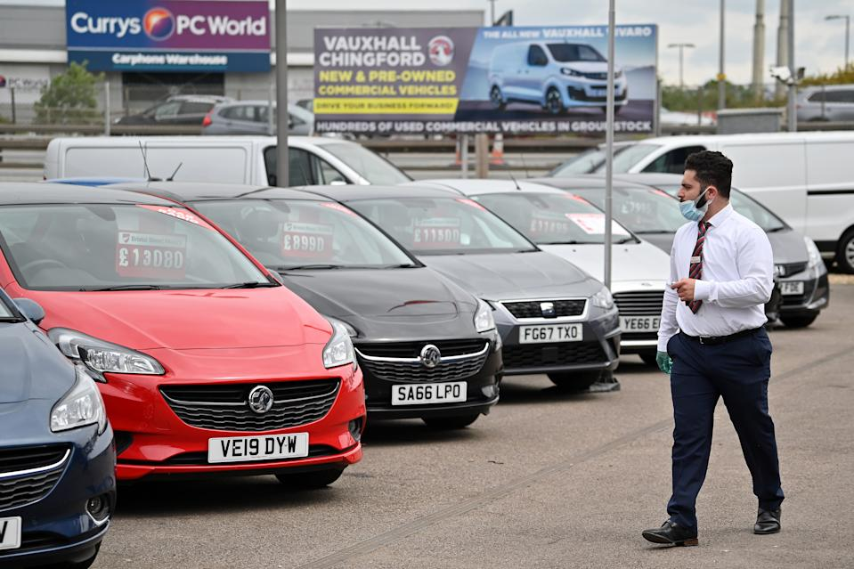 A car sales person wearing PPE (personal protective equipment) including a face mask and gloves as a precautionary measure against COVID-19, walks past vechiles parked on the forecourt of a recently re-opened Vauxhall car dealership in north London on June 4, 2020, as lockdown restrictions are eased during the noel coronavirus COVID-19 pandemic. - Car showrooms in England reopened this week as the UK government eased COVID-19 lockdown measures that have slammed the brakes on the industry. (Photo by JUSTIN TALLIS / AFP) (Photo by JUSTIN TALLIS/AFP via Getty Images)