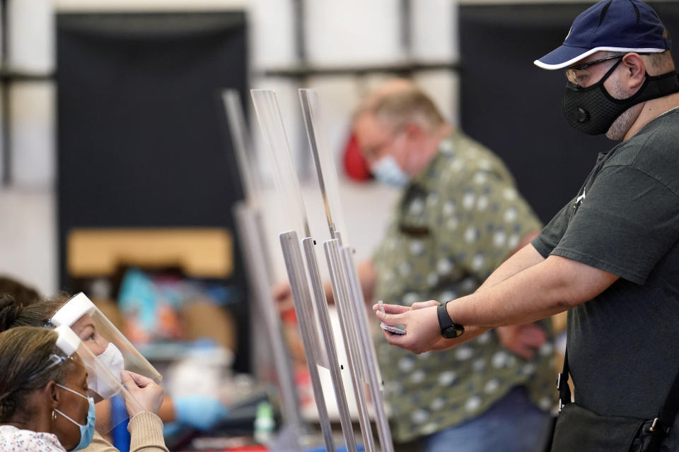 A voter, right, shows his identification to a Harris County election clerk before voting, Tuesday, July 14, 2020, in Houston. (AP Photo/David J. Phillip)