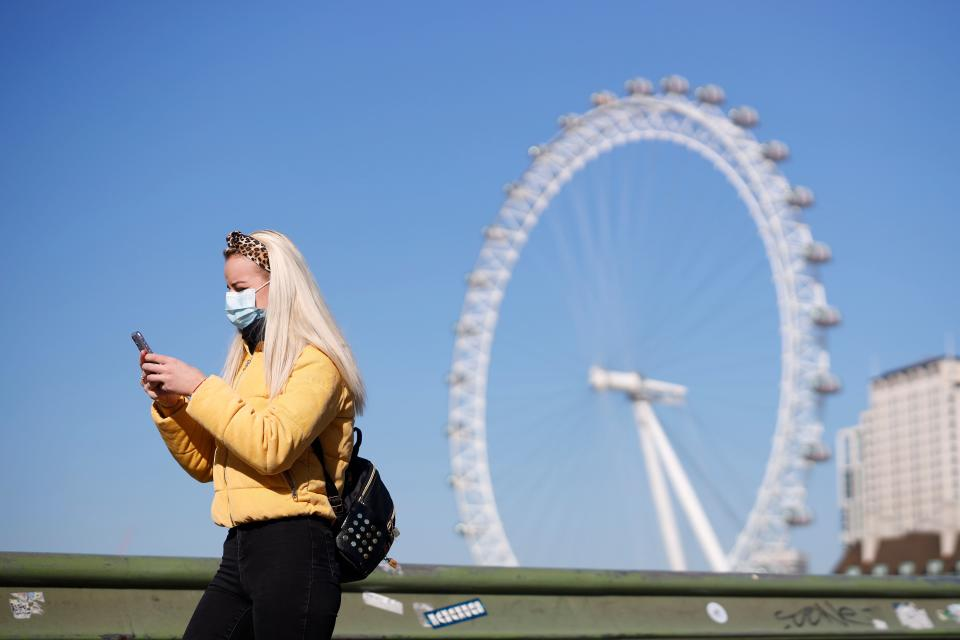"A pedestrian in a mask walks along Westminster Bridge with the London Eye in the backgroud, in a quiet central London on March 25, 2020, after Britain's government ordered a lockdown to slow the spread of the novel coronavirus. - Britain was under lockdown, its population joining around 1.7 billion people around the globe ordered to stay indoors to curb the ""accelerating"" spread of the coronavirus. (Photo by Tolga Akmen / AFP) (Photo by TOLGA AKMEN/AFP via Getty Images)"