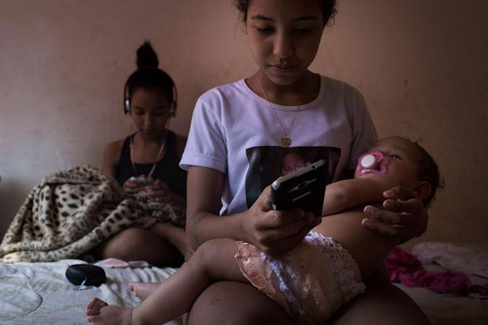 """Nayane and her twin Nayara (in the back) send messages on their phones in their mother's house in Parque Uniao, a shantytown in Rio de Janeiro, Brazil in August 2016. """"A 30-year old single woman with no children is not normal- A man is?- Yes, it is normal in man,"""" says Nayara. For her, a woman, regardless of her schooling , """"must marry and become a mother"""", because the opposite is not natural. (Photo: Rafael Fabrés)"""