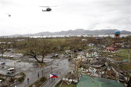 Helicopters hover over the damaged area after super Typhoon Haiyan battered Tacloban city, central Philippines, November 9, 2013. REUTERS/Romeo Ranoco