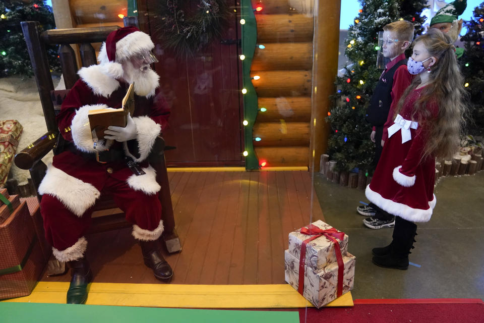William Peargin, 8, and Payton Peargin, 8, right, stand six feet from Santa Claus, who sits behind a sheet of plexiglass, at Bass Pro Shop in Rancho Cucamonga, Calif., on Dec. 4, 2020. In this socially distant holiday season, Santa Claus is still coming to towns (and shopping malls) across America but with a few 2020 rules in effect. (AP Photo/Ashley Landis)