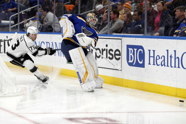 St. Louis Blues goaltender Jake Allen, right, clears a puck from behind the net as Los Angeles Kings' Tyler Toffoli (73) watches during the third period of an NHL hockey game Monday, Nov. 19, 2018, in St. Louis. (AP Photo/Jeff Roberson)