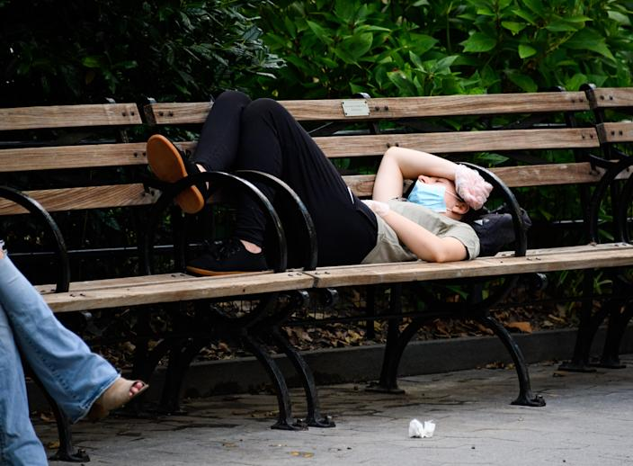 A person wears a mask and gloves while lying on a bench in Madison Square Park, New York. An 'extraordinary' number of people who overcome the coronavirus are said to be developing fatigue. (Getty Images)